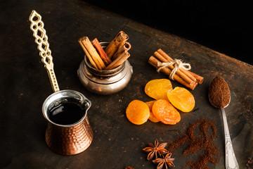 Cafetera Turca y Café en granos y molido sobre fondo oscuro con albaricoques, canela y anís estrellado.. Vista superior