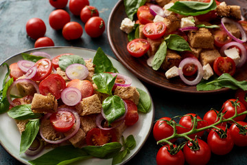 fresh Italian vegetable salad panzanella served on plates on table with tomatoes