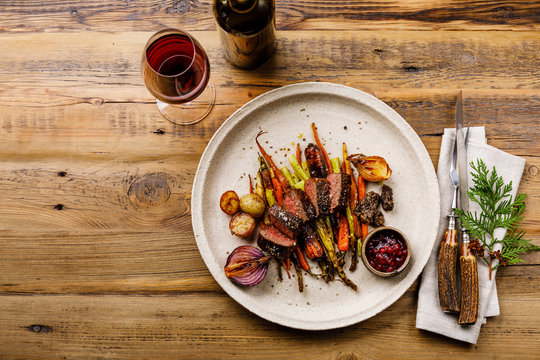 Grilled sliced Venison Steak with baked vegetables and berry sauce and Red wine on wooden background