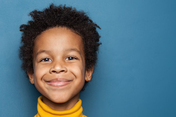 Smiling kid boy portrait. Little african american child boy on blue background