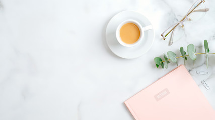 Cozy home office desk table with pink paper notebook, glasses, eucalyptus leaf, coffee cup on marble background. Top view, flat lay, copy space. Elegant feminine workspace with stylish accessories