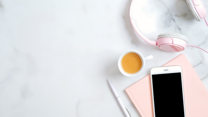 Flat lay home office desk. Women workspace with headphones, smartphone with empty screen mockup, pink paper notebook, pen, coffee cup. Top view feminine background.