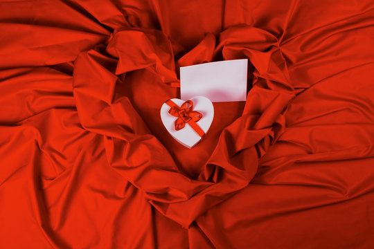 valentines greeting card. white cardboard box in shape of heart wrapped in ribbon and blank paper lay on a red cloth which repeats the form of present package. love and romance gift concept
