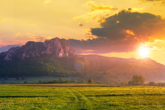 rock formation on the field at sunset. beautiful rural landscape in mountains. wonderful scenery in spring. clouds on the blue sky in evening light. forest on the hills