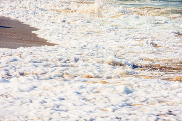 sea waves splash foam on the sunny beach.  mess of salt water and sand in evening light. dynamic nature texture