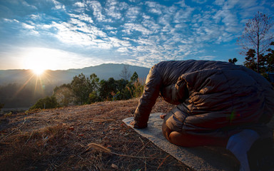 Man kneeling down and praying at sunset on mountain. christian  concept.