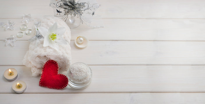 Spa treatments for Valentine's Day. White towel with flower and pearls on a white wooden background with a red heart and candles with copy space. Beauty salon