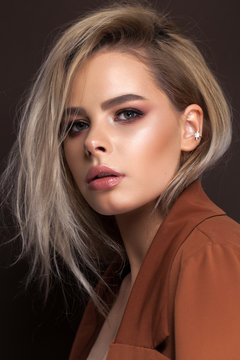 A very beautiful young blonde model with professional make up, perfect skin. Trendy red toned smokey eyes and nude lips.