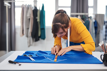 Creative caucasian fashion designer standing in her studio and drawing scheme on blue linen for a beautiful night dress.