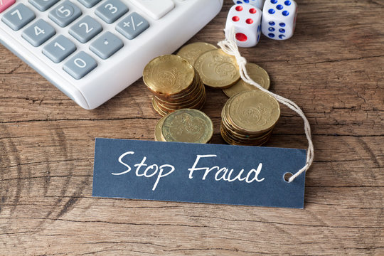 Conceptual image of the words Stop Fraud written on label tag with coins,dice and calculator