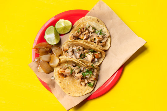 "Mexican beef tacos also called ""suadero"" on yellow background"