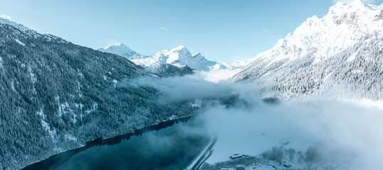 Panoramic view of scenic idyllic winter landscape in the Swiss Alps with forest covered in snow and mighty mountains by the lake.