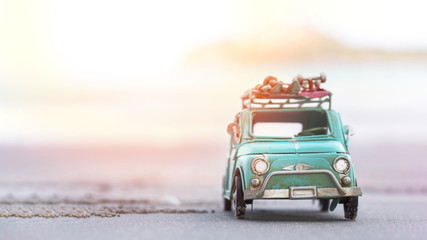 Miniature tin car closeup at summer beach scene