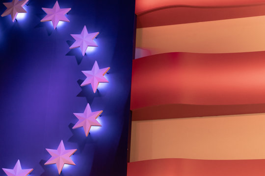 An early American flag showing thirteen stars in lights.