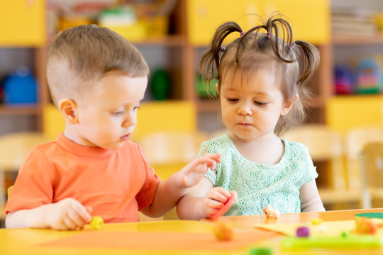 Toddlers boy and girl playing at table with educational toys. Children infants in creche or daycare.