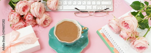 Female workspace with laptop, beautiful pink roses flowers, gift box, accessories, notebooks , glasses, cup of coffee.flat lay top view women's office desk banner on pink background.  copy space