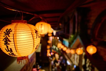 Poster Japon Closeup of Chinese paper lantern with lights surrounded by buildings with a blurry background