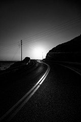 Recess Fitting Gray traffic Greyscale of a curvy road surrounded by hills under sunlight