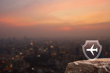 Airplane with shield flat icon on rock mountain over blur of cityscape on warm light sundown, Business travel insurance and safety concept