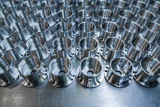 a batch of shiny metal cnc aerospace parts production - close-up with selective focus for industrial background