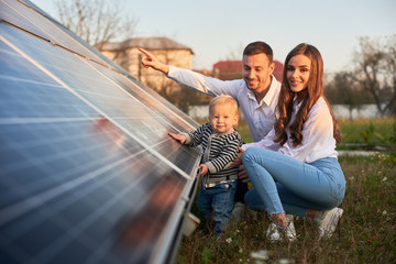 A young family of three is crouching near a photovoltaic solar panel, smiling and looking at the...