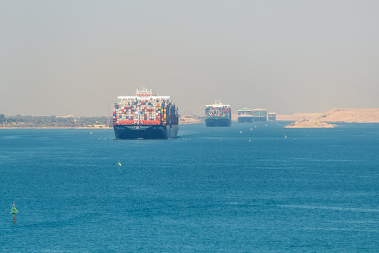 Suez, Egypt - November 5, 2017: Large container vessels (ship) passing Suez Canal in the sandy haze in Egypt.