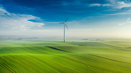 Wind turbine on green field at sunrise, view from above