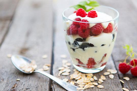 Healthy yogurt dessert with muesli, raspberries and black currants.