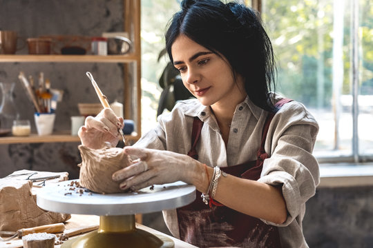 Craftsperson Concept. Young woman making pottery indoors making shape for clay using tool smiling joyful working process