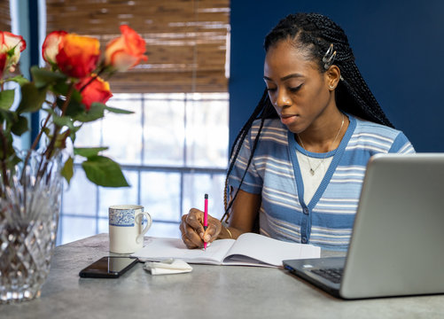Young, African American woman working from home on her laptop in the kitchen.
