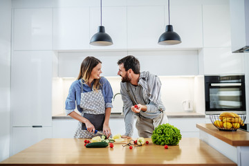 Young charming smiling caucasian woman in apron standing in kitchen and cutting cucumber while talking with her boyfriend. Man holding cherry tomato and talking about healthy lifestyle. Papier Peint