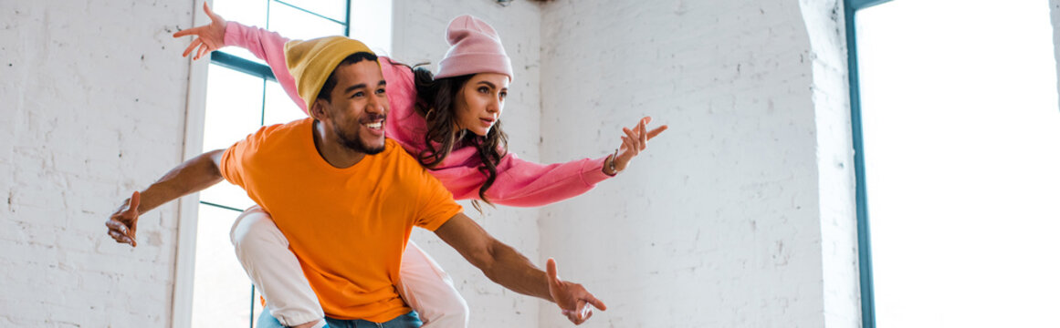 panoramic shot of attractive girl with outstretched hands breakdancing with african american man in hat