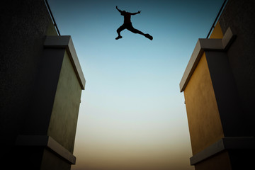 Concept of jumping over obstacles, The silhouette of a man jumping between two tall buildings.