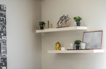 White wall. Shelves with statuettes and flowers. Decor of the interior.