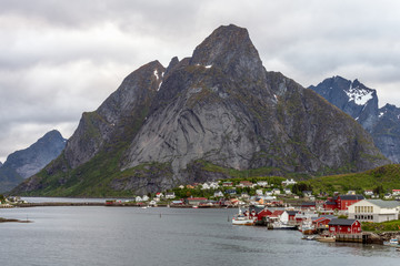 Aerial shot ofThe city of Reine in Lofoten/Norway. The famous Mount Olstind and snow covered mountains in the background. Traveling and Norwegian concept.