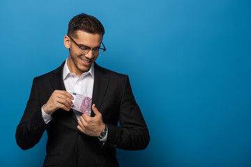 Smiling businessman putting dollar banknotes in jacket pocket on blue background