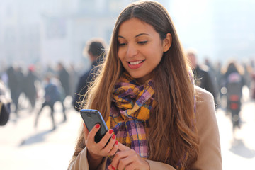 Happy beautiful young woman typing on smart phone outdoor with blurred crowd of people on street background, selective focus. City lifestyle people technology.