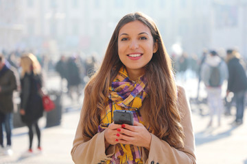 Happy beautiful young woman looking at camera and holding mobile phone outdoor with blurred crowd of people on street background, selective focus. City lifestyle people technology.