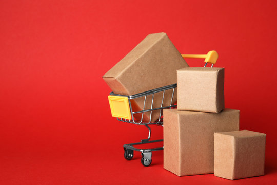 Shopping cart and boxes on red background, space for text. Logistics and wholesale concept