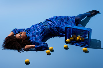 african american woman lying with shopping basket and lemons on blue background