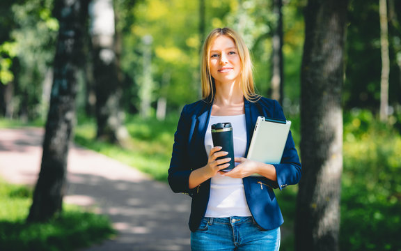 Young happy smiling caucasian adult girl business student walking concept in the summer green park outdoor holding tablet and coffee thinking of credit money finance people job in the college