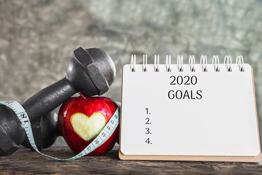 2020 goals for sport concept with red apple,dumbbell and resolution list on calendar