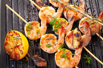 grilled shrimp on skewers. Grilled seafood on skewers with spices, herbs and lemon. delicious prawn. Grill. The iron grill. close up
