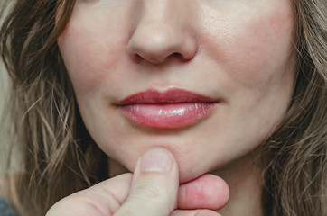Male finger on the female chin below the lips. Hand holds chin