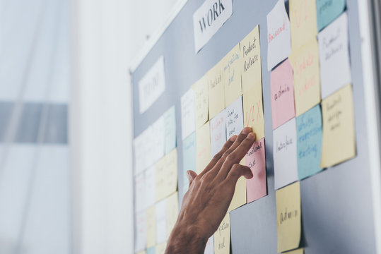 cropped view of businessman touching sticky notes with letters in office