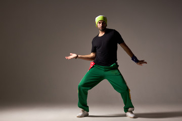 Cool looking dancing hip hopper in sportswear training in dance studio, showing new element, exercising hip hop movie, , male dancer of soul r and b, street dance, isolated on gray background