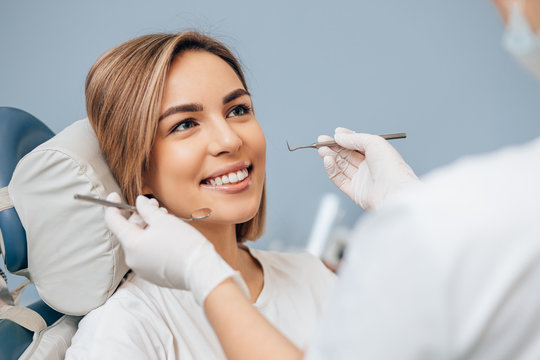 attractive woman with short hair sit in dental office and look at doctor with confidence, she has perfect smile. professional doctor of clinic use special sterilized medical instruments
