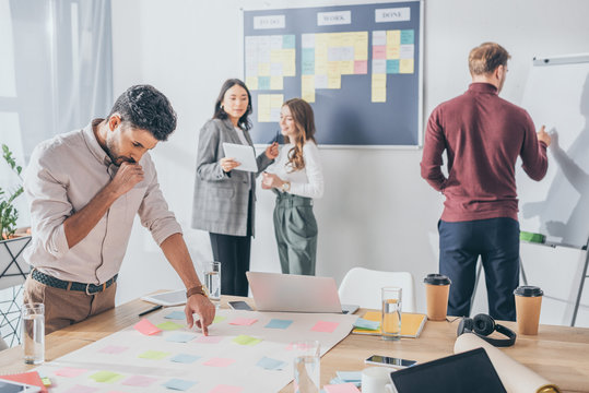 selective focus of pensive mixed race scrum master pointing with finger at sticky note near coworkers