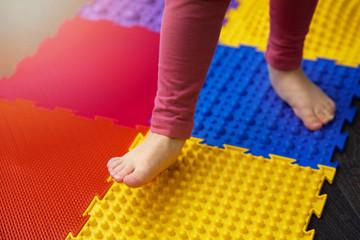 child walking on orthopedic feet massage puzzle floor mat