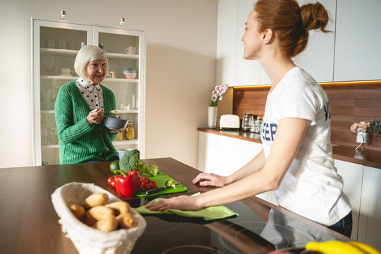 Delighted young volunteer cleaning kitchen for pensioner